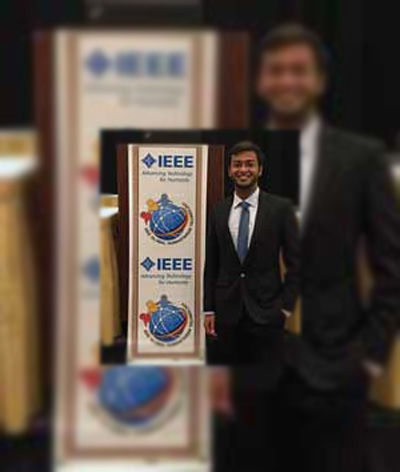 Farhan Faisal at IEEE Global Humanitarian Technology Conference 2016, standing next to the IEEE poster.