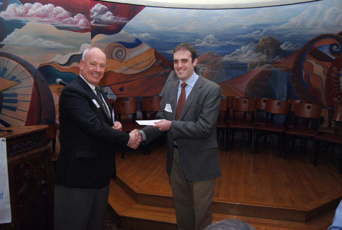 James Pena receiving scholarship in front of a painting